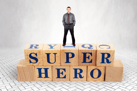 Self Confident adult Caucasian man stands on the top of heap of wooden blocks with a text Super Hero