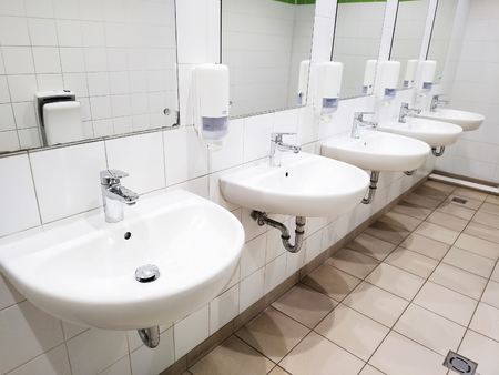 Many washing basins with mirrors on the wall in a public toilet