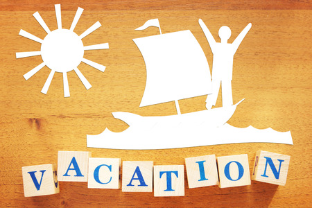 Summer Vacation at Seaside. Conceptual image with paper cuttings and wooden cubes on a desk Banque d'images