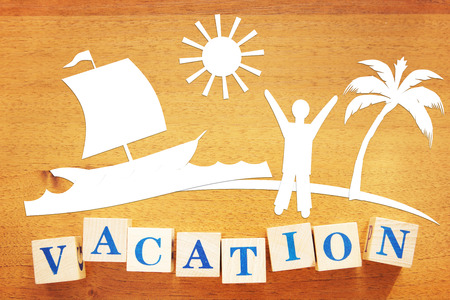 Concept of a Summer Vacation at Seaside. Paper cuttings and wooden cubes on a desk
