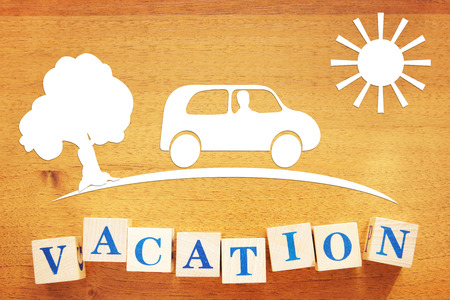 Concept of a Vacation and Traveling by Car. Paper cuttings and wooden cubes on a desk
