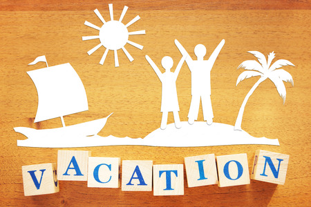 Concept of a Vacation at Seaside. Paper cuttings and wooden cubes on a desk Stockfoto