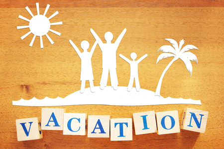 Family vacation at seaside. Conceptual image with paper cuttings and wooden cubes on a desk