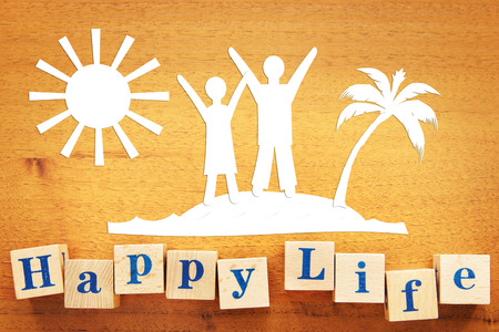 Happy Lifestyle and a Vacation. Concept with paper cuttings on a wooden desk
