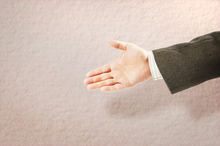Man in a suit reaches his hand out with open palm for handshaking. Beige background with copy space