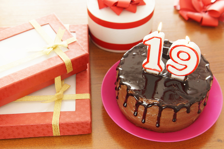 Birthday celebration at nineteen years. A cake with burning candles in the form of numbers and a lot of gifts on a table Stock Photo