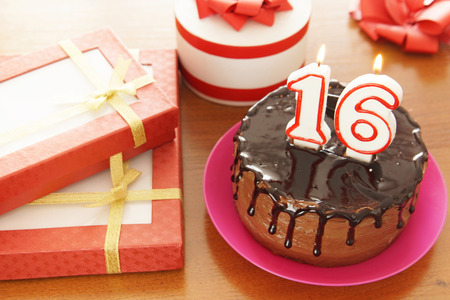Birthday celebration at sixteen years. A cake with burning candles in the form of numbers and a lot of gifts on a table