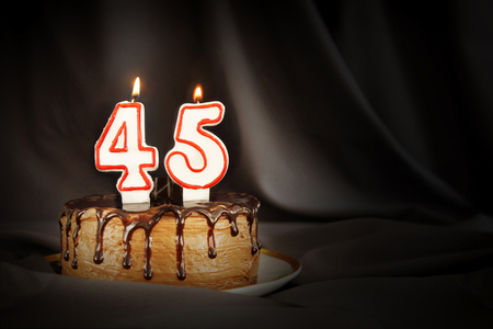 Forty five years anniversary. Birthday chocolate cake with white burning candles in the form of number Forty five. Dark background with black cloth