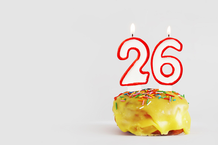 Twenty six years anniversary. Birthday cupcake with white burning candles with red border in the form of number Twenty six. Light gray background with copy space Imagens