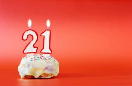 Twenty one years birthday. Cupcake with white burning candle in the form of number 21. Vivid red background with copy space