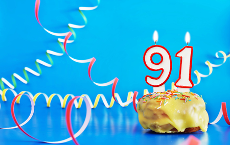 Birthday of ninety one years. Cupcake with white burning candle in the form of number 91. Vivid blue background with copy space