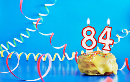 Birthday of eighty four years. Cupcake with white burning candle in the form of number 84. Vivid blue background with copy space 스톡 콘텐츠