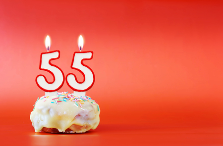 Fifty five years birthday. Cupcake with white burning candle in the form of number 55. Vivid red background with copy space 스톡 콘텐츠