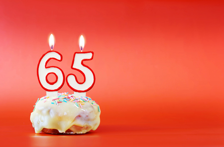 Sixty five years birthday. Cupcake with white burning candle in the form of number 65. Vivid red background with copy space