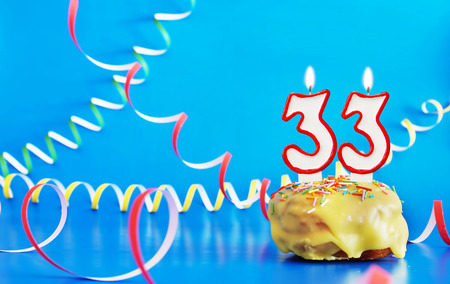 Birthday of thirty three years. Cupcake with white burning candle in the form of number 33. Vivid blue background with copy space