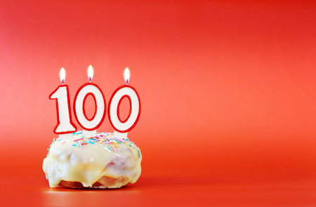 One hundred years birthday. Cupcake with white burning candle in the form of number 100. Vivid red background with copy space Foto de archivo