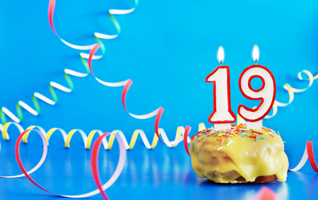 Birthday of nineteen years. Cupcake with white burning candle in the form of number 19. Vivid blue background with copy space Stock Photo