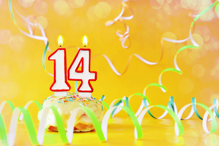 Fourteen years birthday. Cupcake with burning candles in the form of number 14. Bright yellow background with copy space
