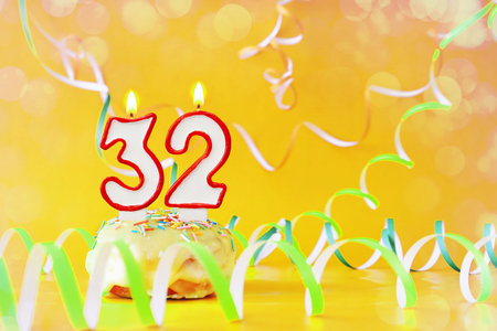 Thirty two years birthday. Cupcake with burning candles in the form of number 32. Bright yellow background with copy space