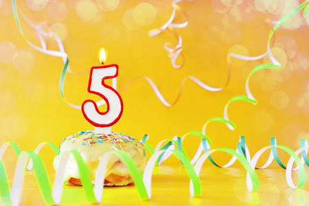 Five years birthday. Cupcake with burning candle in the form of number 5. Bright yellow background with copy space Archivio Fotografico
