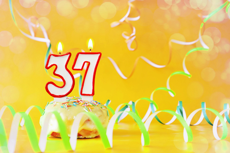 Thirty seven years birthday. Cupcake with burning candles in the form of number 37. Bright yellow background with copy space Imagens