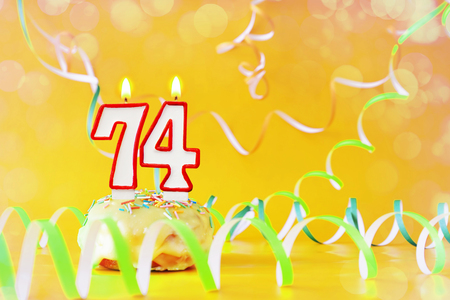 Seventy four years birthday. Cupcake with burning candles in the form of number 74. Bright yellow background with copy space