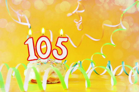 One hundred and five years birthday. Cupcake with burning candles in the form of number 105. Bright yellow background with copy space