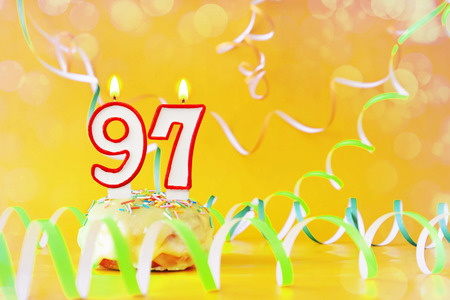 Ninety seven years birthday. Cupcake with burning candles in the form of number 97. Bright yellow background with copy space