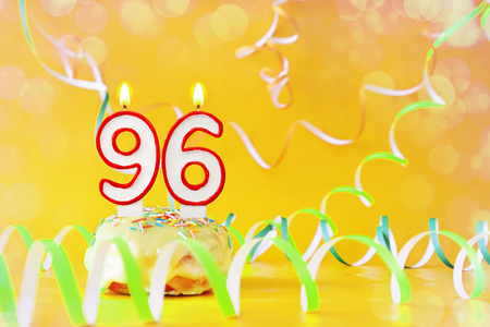 Ninety six years birthday. Cupcake with burning candles in the form of number 96. Bright yellow background with copy space