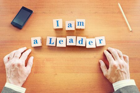 I am a leader. Businessman made text from wooden cubes on a desk