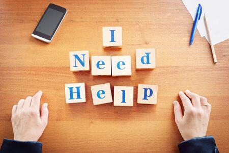 Ich brauche Hilfe. Geschäftsfrau machte Text aus Holzwürfeln auf einem Schreibtisch Standard-Bild