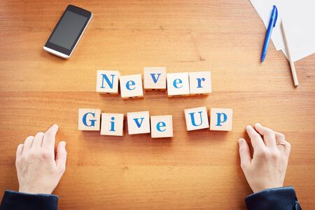 Never give up. Business woman made text from wooden cubes on a desk