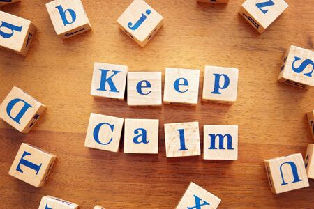Keep calm. Conceptual image with the text made from wooden cubes on a desk Imagens
