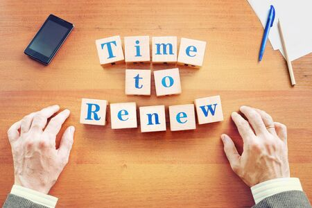 Time to renew. Businessman made text from wooden cubes on a desk