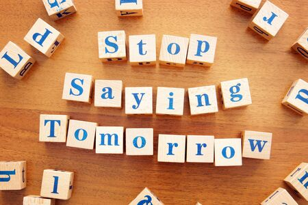 Stop saying tomorrow. Conceptual image with the text made from wooden cubes on a desk