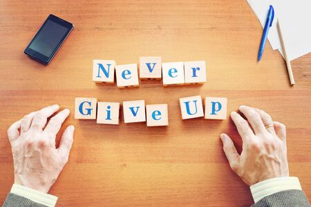 Never give up. Businessman made text from wooden cubes on a desk Imagens