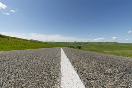 Beautiful summer landscape with an asphalt highway going on green hills in a sunny day. Focus on foreground