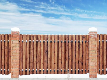 Span of the new wooden fence between the brick pillars. Winter view against the blue sky