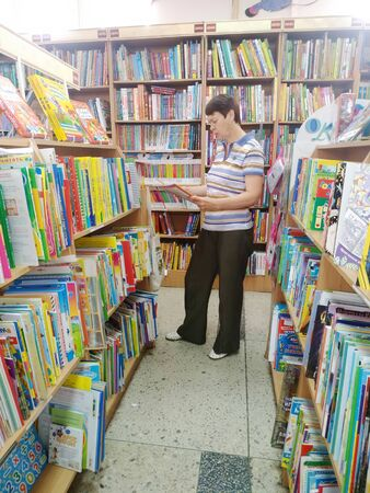 KEMEROVO, RUSSIA, AUGUST 19, 2019. Woman is choosing books among bookshelves in the bookstore Dekart