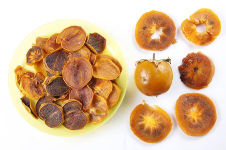 Ingredients for healthy fruit chips made of persimmon on white background. Vegetarian dietary food