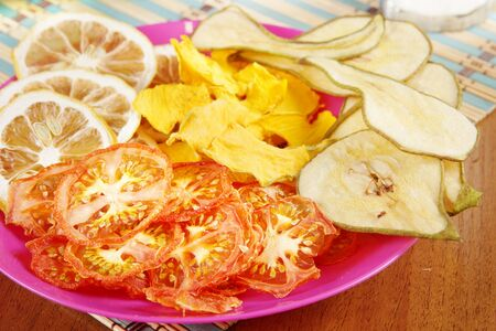 Many various fruit and vegetable chips lie in a plate. Healthy and tasty vegetarian food