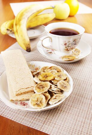 Tea with fruit chips made of bananas and crispbreads. Healthy vegetarian dietary breakfast