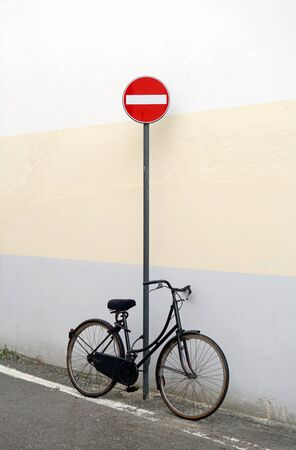 Old retro bicycle stands on the street by the road sign No Entry near the wall of the house