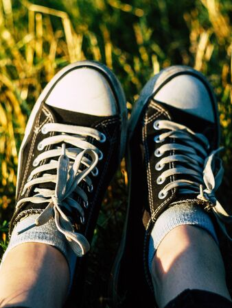 female beautyfull legs in sneakers on the summer grass in the park