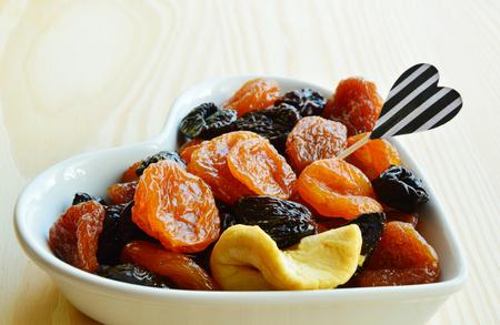 ciruela pasa: frutos secos en un tazón en forma de corazón y fruta palillo de dientes con mesa de madera. frutos secos manzana, pera, ciruela, albaricoque.