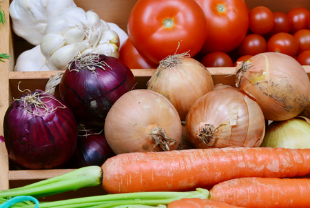 carots: Carrots, onion, red onion, garlic, tomatoes, potatoes. a lot of colorful vegetable in the kitchen.