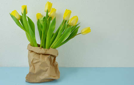 yellow tulips in brown paper bag on the table with wall background