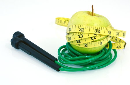 Jumping rope and eat fruit to lose weight. (Soft focus, lens blur) Green apple and jump rope on white background. Jumping rope is great calorie burner.