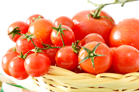 Why You Should Be Eating More Tomatoes. Many tomatoes in the basket. Stock Photo