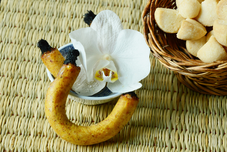 scented candle: Thai shortbread cookies or Kleeb Lamduan is Thai name. Thailand dessert and fragrant or scented candle used for smoking sweetmeats. Stock Photo